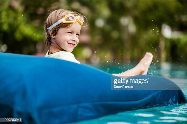 small cute boy enjoying floating and splashing at the pool - kids pool games stock pictures, royalty-free photos & images