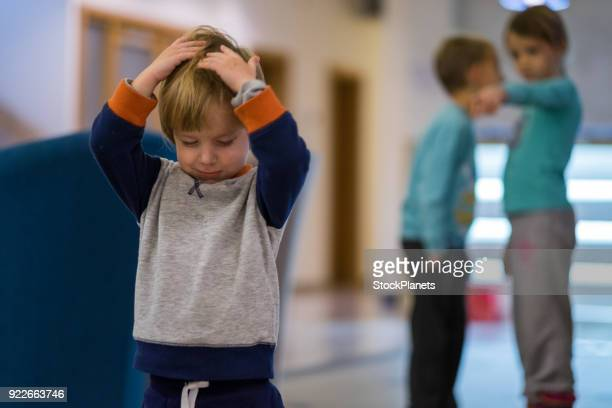 Small cute boy is sad because the other kids gossip him