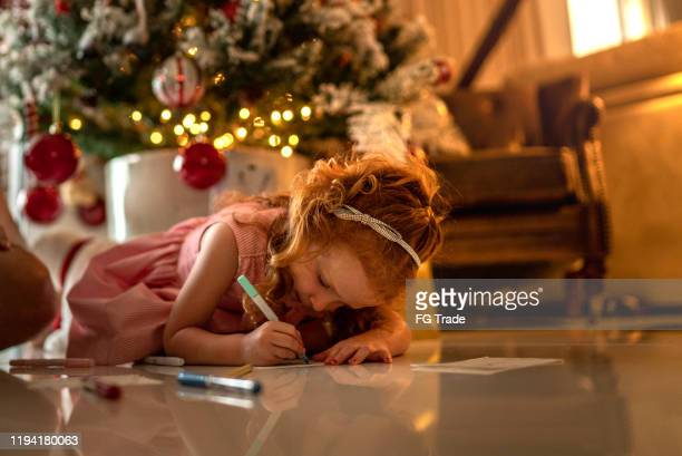 small cute girl writing letter to santa at home - correspondence stock pictures, royalty-free photos & images