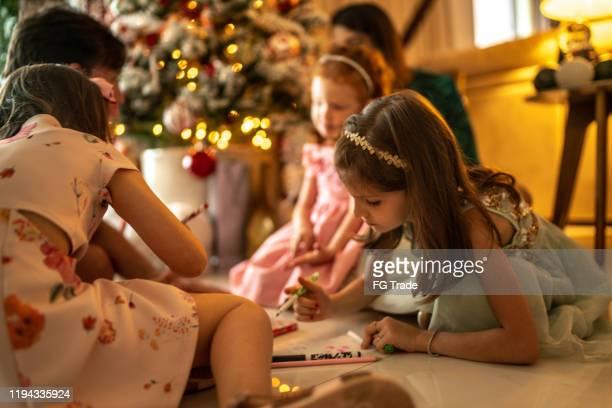 meninas bonitos pequenas que escrevem a letra a santa em casa - responder - fotografias e filmes do acervo