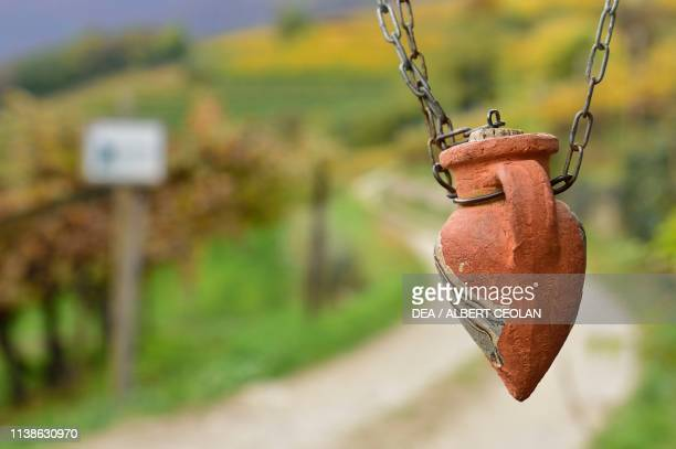 Small decorated clay amphora hanging from a chain Sudtiroler Weinstrasse TrentinoAlto Adige Italy