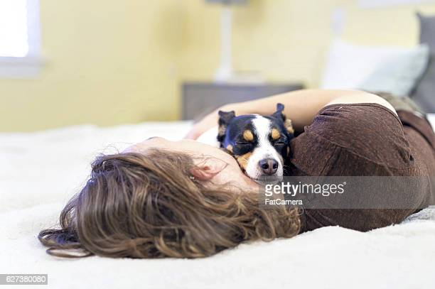 Small dog sleeping with his owner on the bed