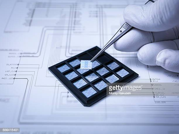 Small electronic chips held in tweezers in laboratory, close up