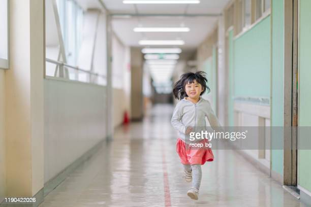 small elementary girl running in hallways at school - east asian ethnicity stock pictures, royalty-free photos & images