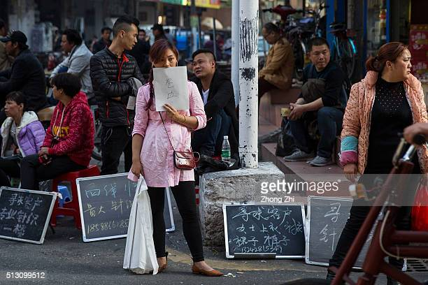 Small fabric factories owners look for hiring workers and taking clients and orders at street at Kanglecun one of the urban villages in Guangzhou on...