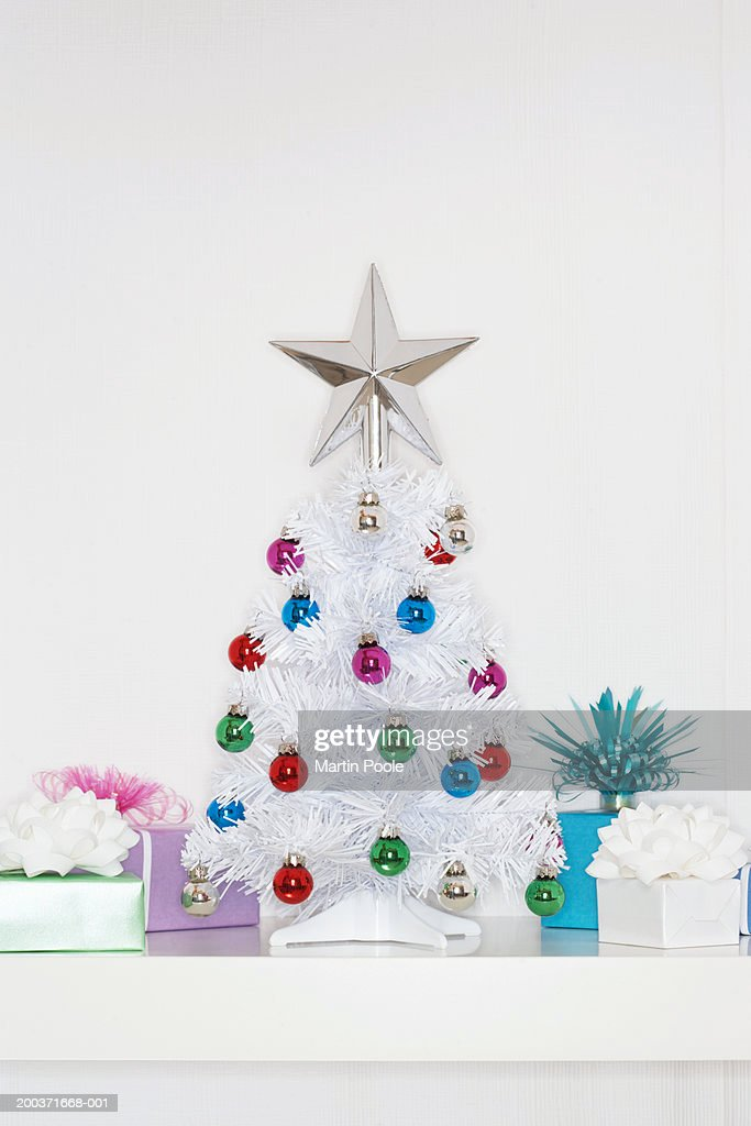 small fake christmas tree surrounded by gifts close up stock photo