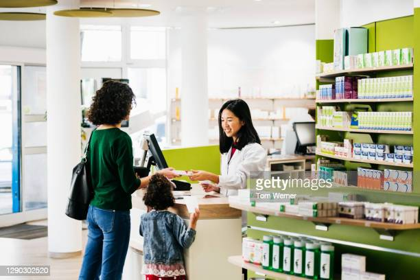 small family being served by chemist at local pharmacy - healthcare stock pictures, royalty-free photos & images