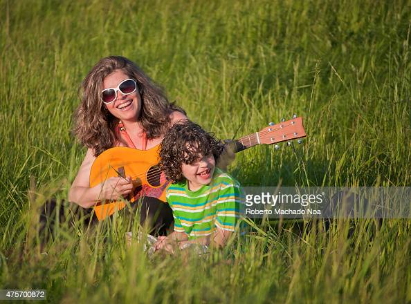 Small Family Playing Accoustic Guitar Outdoors Happy