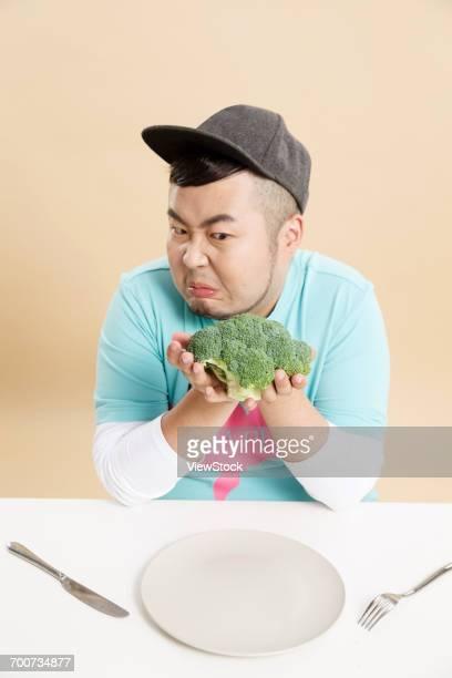 Small fat man holding broccoli