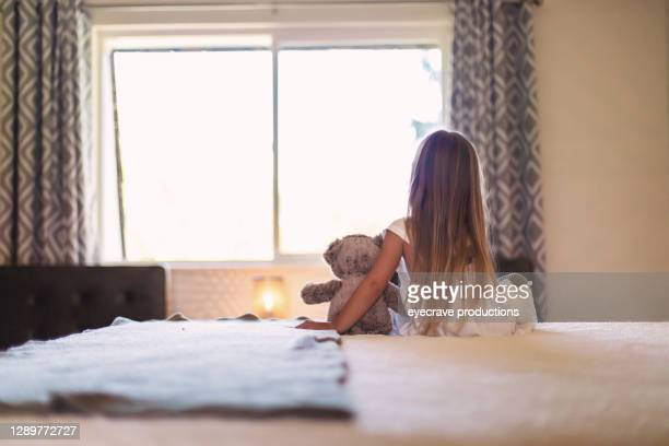 small female child sitting on bed with teddy bear photo series - eyecrave  stock pictures, royalty-free photos & images