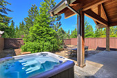 Small fenced  back yard space with dining room table  and hot tub surrounded by trees