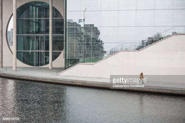 small figure of a man walking in front of the marie-elisabeth lüders building, a parliamentary building in berlin, germany. - istock photos et images de collection