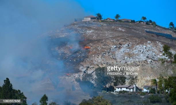 Small fires break out on a hillside in West Hills California near Bell Canyon Road on November 11 as firefighters continue their battle to control...