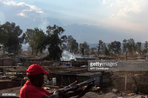 TOPSHOT A small firework fired by protestors explodes amongst shacks in the Sicelo settlement in Meyerton south of Johannesburg on July 4 during...