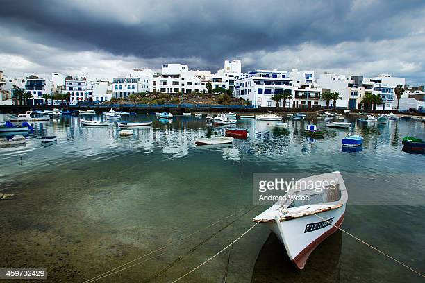 CONTENT] A small fishing boat properly tied to the shore of the lagoon Charco de San Gines in Arrecife capital of Lanzarote island Black clouds loom...