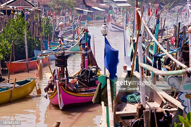 CONTENT] Small fishing boats moored on the banks of a small river estuary This is the small traditional fishing village of Tamansari near Probolingo...