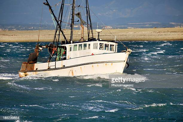Small fishing trawler in rough seas, New Zealand