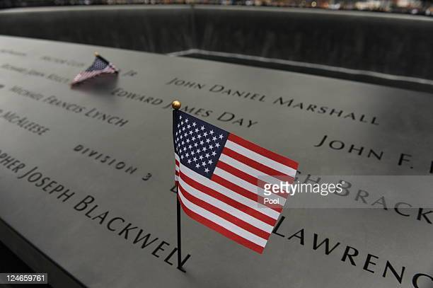 Small flags are left on the bronze plaques that bear the names of the victims of the September 11 terror attacks that surround the perimeter of the...