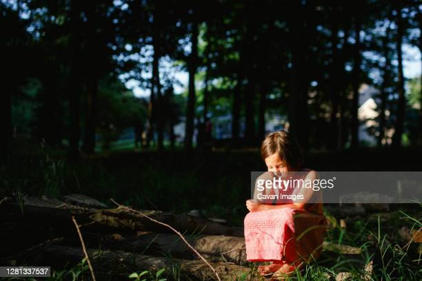 a small forlorn child sits in sunlight in a shaded patch of woods - sadgirl stock pictures, royalty-free photos & images