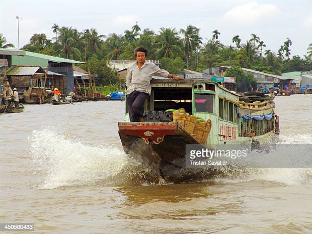 Small freight boat sailing on the Mekong river . Other keywords: Nautical Vessel, Outdoors, People, Transportation, man, speed, water splashing.