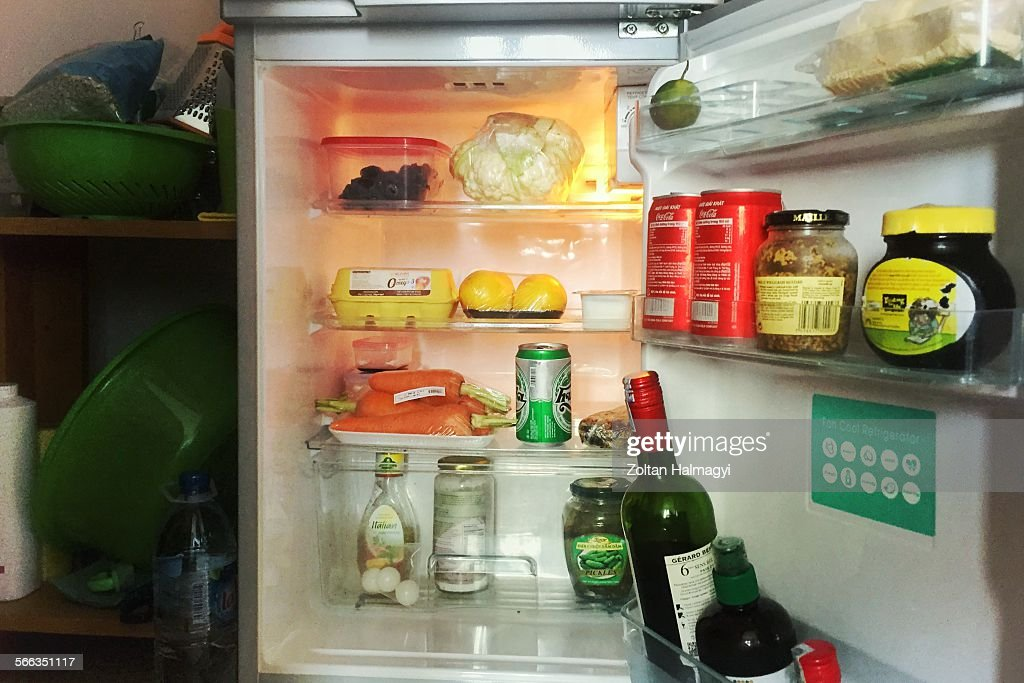 Small fridge in a cluttered apartment News Photo - Getty Images