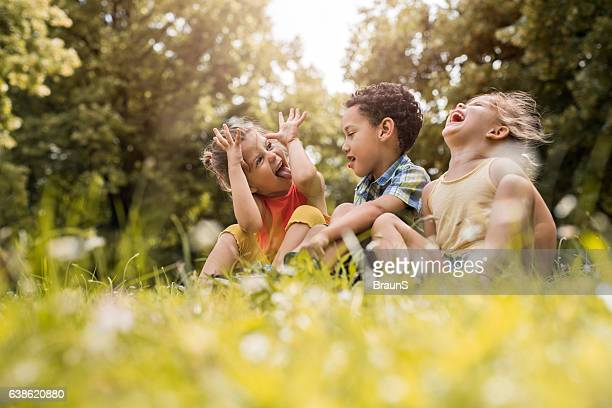 small friends having fun while relaxing in grass. - rindo - fotografias e filmes do acervo
