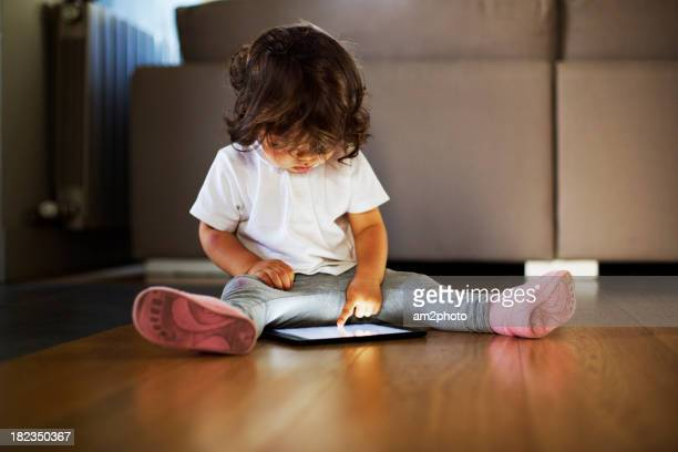 Small giellooking at a tablet on the floor