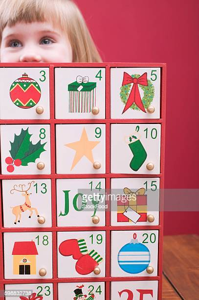 small girl behind advent calendar - advent calendar stock photos and pictures