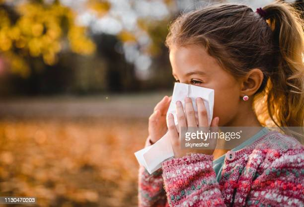 small girl blowing her nose into a napkin outdoors. - cold virus stock pictures, royalty-free photos & images
