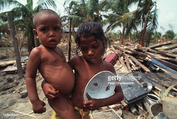 A small girl carries her brother and a plate through the wreckage of their village devastated by one of the biggest cyclones to hit Bangladesh in...