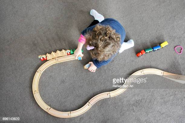 Small girl child assembling a wooden railway outlet