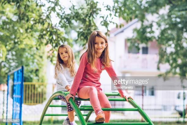 small girl climbing at playground - 6 7 anni foto e immagini stock