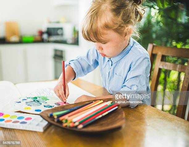 Small girl coloring the book