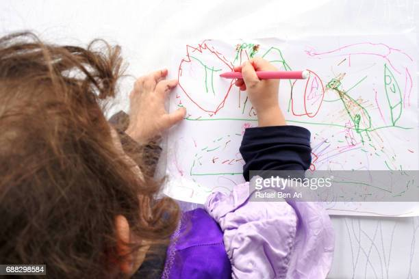 small girl drawing a picture - rafael ben ari stock pictures, royalty-free photos & images