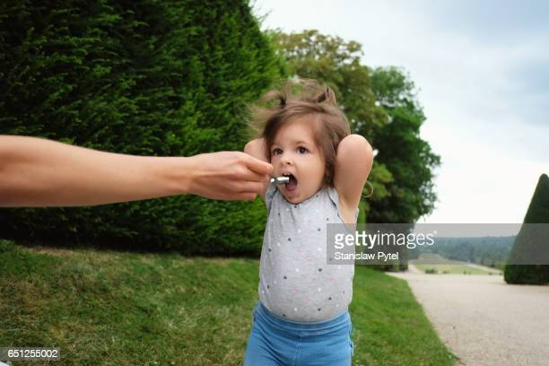 Small girl eating in park