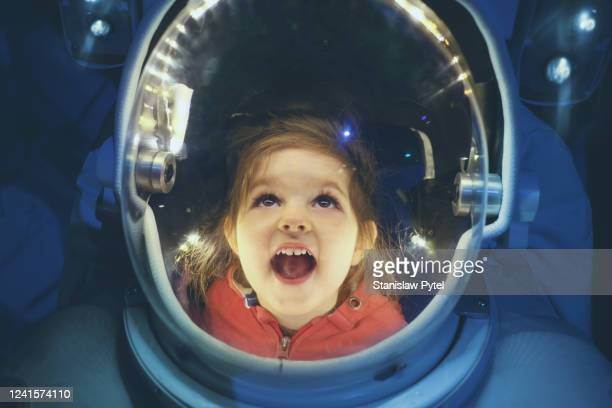 small girl enjoying being inside of astronaut suit - discovery stock pictures, royalty-free photos & images
