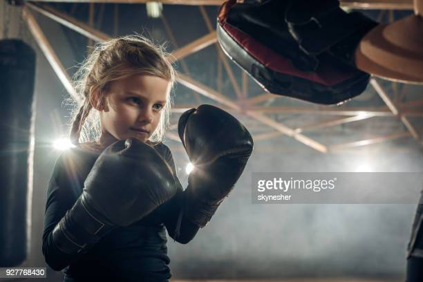 Kleine Mädchen Boxen mit unkenntlich Trainer in einem Fitnessstudio trainieren.