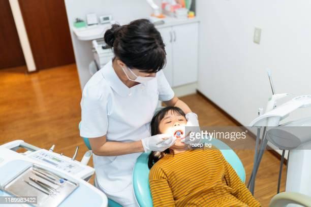 歯医者で検診を受ける小さな女の子 - シカ ストックフォトと画像