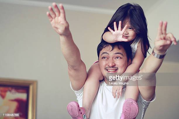 small girl getting shoulder back ride - carrying a person on shoulders stock photos and pictures
