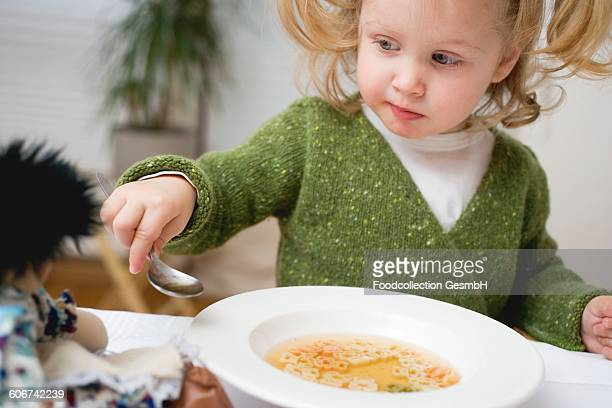 Small girl giving her doll a spoonful of soup