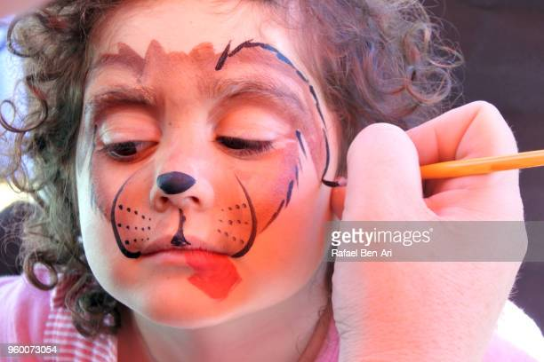 small girl having a face painting of a dog face - rafael ben ari bildbanksfoton och bilder