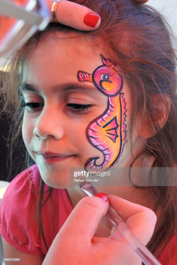 Small girl having a face painting  of a seahorse fish : Stock Photo