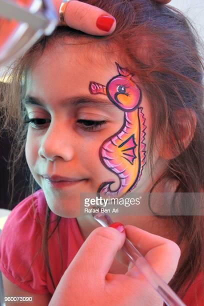 small girl having a face painting  of a seahorse fish - rafael ben ari bildbanksfoton och bilder