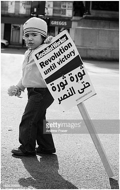 Small girl holding a doll and a 'Revolution until victory' political placard at a 'Stop The War' demonstration in George Square, Glasgow, Scotland,...