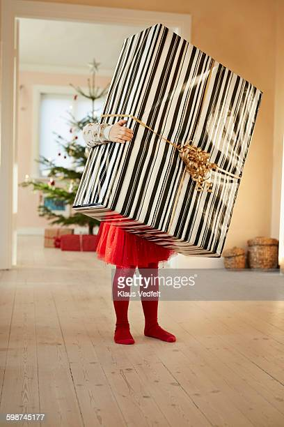 Small girl holding huge christmas present