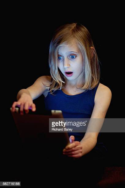 Small girl illuminated by smart phone