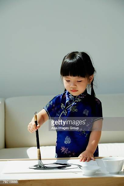 A small girl in blue silk cheongsam writing Chinese calligraphy