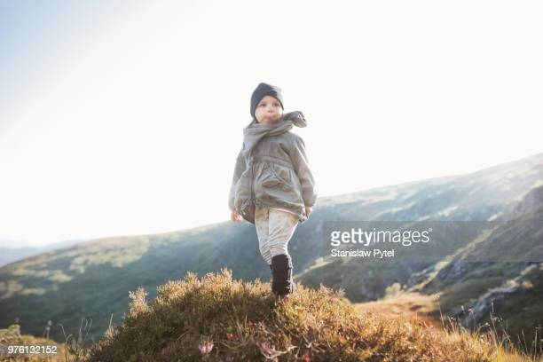 Small girl in mountains at sunset