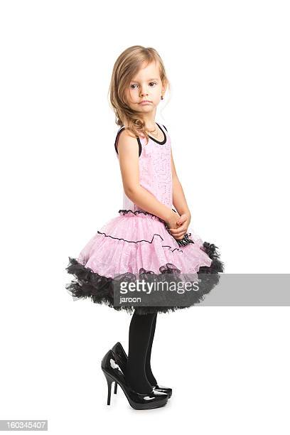 small girl in pink dress wearing her mother shoes - little girl in high heels stock photos and pictures