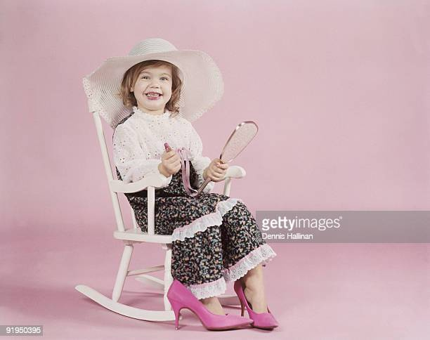 Small girl in rocking chair playing with makeup and adult clothes